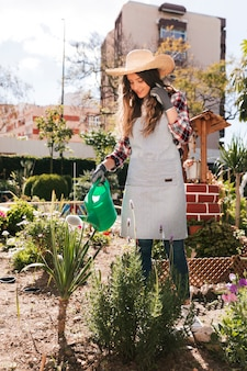 Portret van een glimlachende jonge vrouwelijke tuinman die de installaties in de tuin water geeft