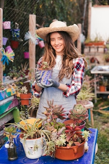 Portret van een glimlachende jonge vrouwelijke tuinman die hoed dragen die geschilderde potinstallatie in serre houden
