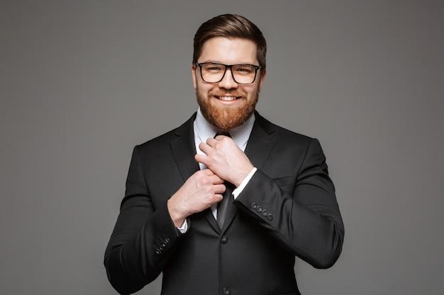 Portret van een glimlachende jonge zakenman gekleed in pak