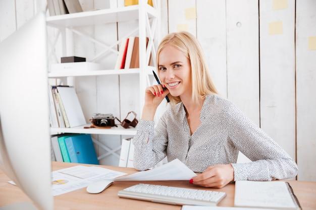 Portret van een glimlachende jonge zakenvrouw die op haar werkplek zit en naar de voorkant kijkt