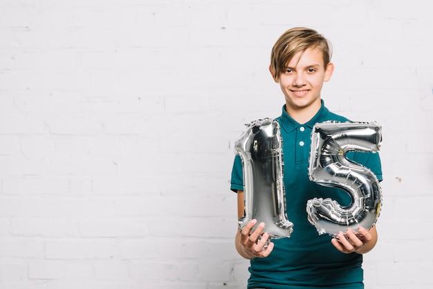 Portret van een glimlachende jongen die cijfer 15 folieballon toont