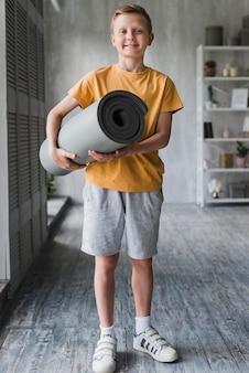 Portret van een glimlachende jongen die grijs opgerolde oefeningsmat ter beschikking houdt