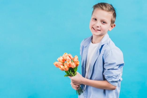 Portret van een glimlachende jongen die verse mooie tulpen houdt die in hand zich tegen blauwe muur bevinden