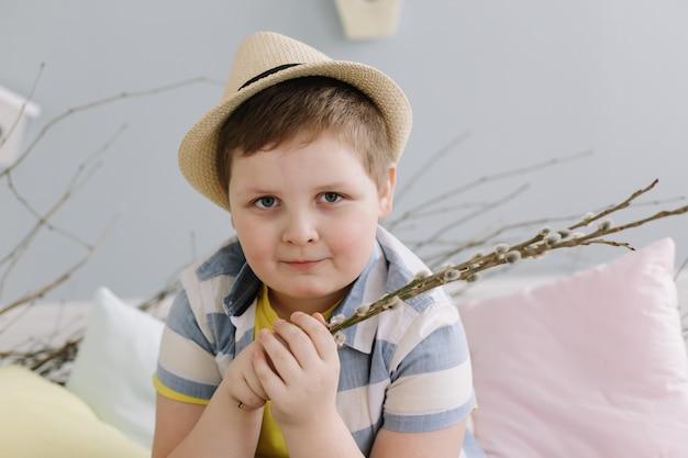Portret van een glimlachende jongen in een de wilgentakken van de hoedenholding