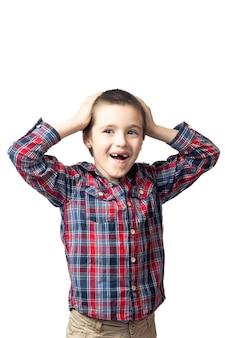 Portret van een glimlachende jongen in een geruit overhemd die zijn hoofd op een witte geïsoleerde achtergrond houdt