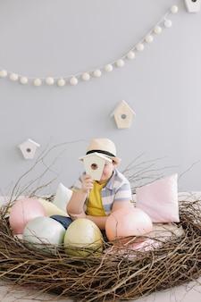 Portret van een glimlachende jongen in een hoed in het decoratieve nest van pasen met paaseieren, droge wilgentakken.