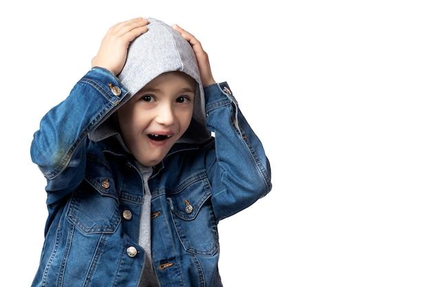 Portret van een glimlachende jongen in een spijkerjasje dat zijn hoofd vasthoudt, vrolijk schreeuwt en zich verheugt over zijn prestaties