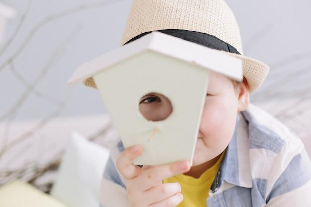 Portret van een glimlachende jongen in een vogelhuisje van de hoedenholding