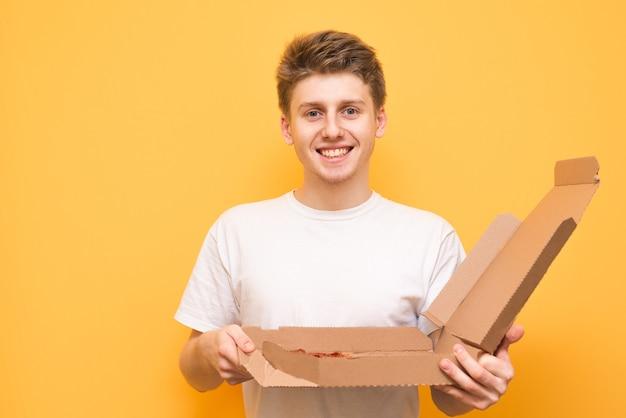 Portret van een glimlachende jongen met een doos met pizza in zijn handen, die de camera onderzoekt
