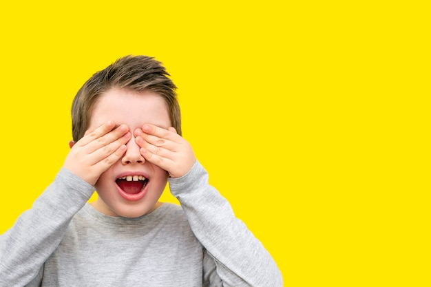 Portret van een glimlachende jongen met gesloten ogen met zijn handpalmen, open mond