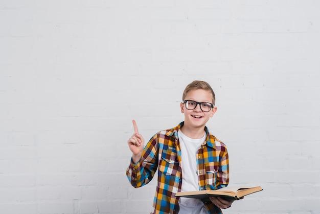 Portret van een glimlachende jongen met oogglazen die een open in hand boek houden die zijn vinger naar omhoog richt