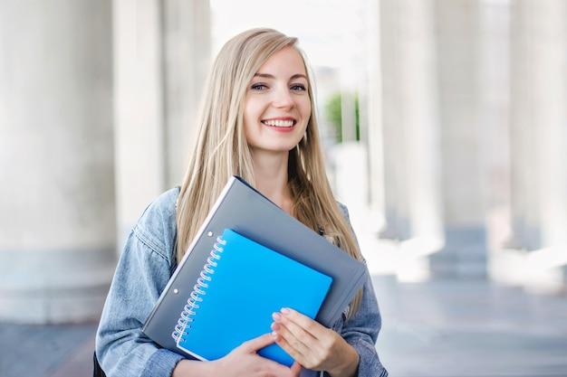 Portret van een glimlachende kaukasische studente die een map en een notitieboekje in haar handen op de achtergrond van een licht gebouw van de universiteit, onderwijsconcept houdt