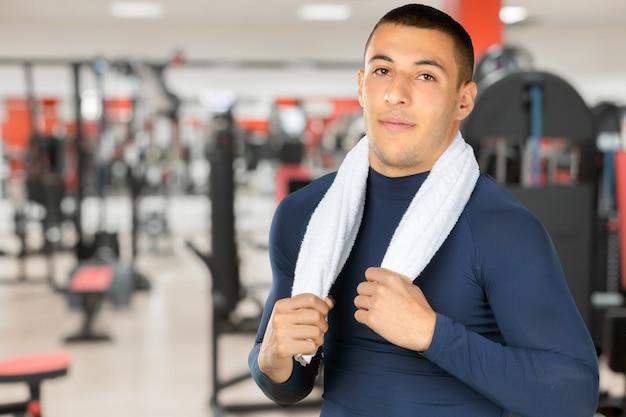 Portret van een glimlachende kerel bij de gymnastiek om geschikt te blijven en gedefinieerde spieren te hebben