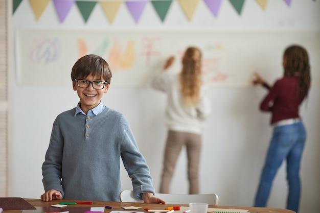 Portret van een glimlachende kleine jongen die een bril draagt en naar de camera kijkt terwijl hij staat door tafel te maken en te genieten van kunstles op school, kopieer ruimte