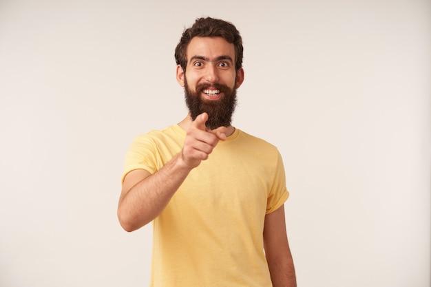 Portret van een glimlachende knappe jonge kerel met een baard wijst met de vinger naar voren en kijkt naar je, blij om te zien opletten tegen de witte muur