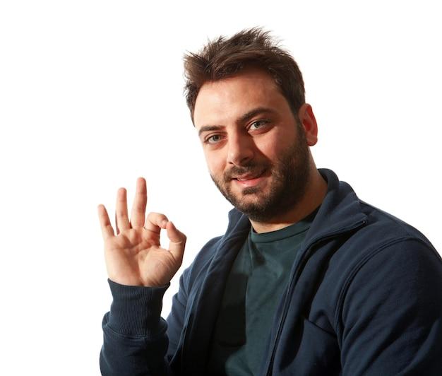 Portret van een glimlachende knappe jonge mens die ok teken over een witte muur gebaart