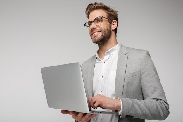 Portret van een glimlachende knappe man in een bril die een laptop vasthoudt en gebruikt die over een witte muur wordt geïsoleerd