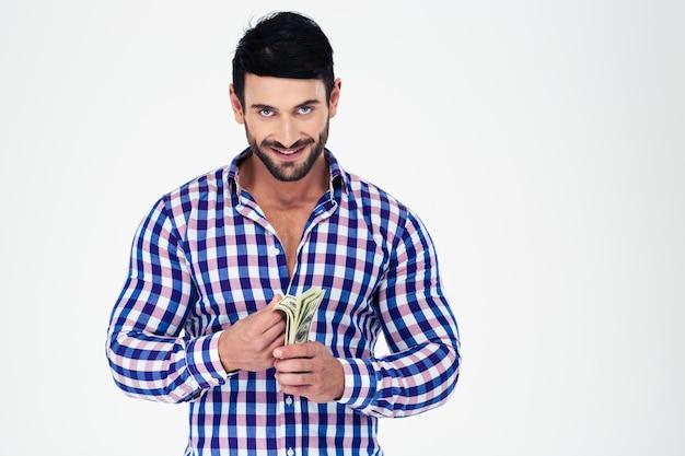 Portret van een glimlachende knappe man met geld geïsoleerd op een witte muur