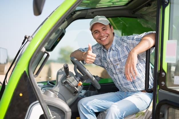 Portret van een glimlachende landbouwer die duimen in zijn tractor opgeeft