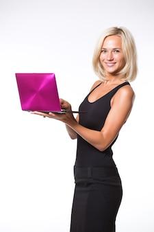 Portret van een glimlachende laptop van de meisjesholding die op een witte achtergrond wordt geïsoleerd en camera bekijkt