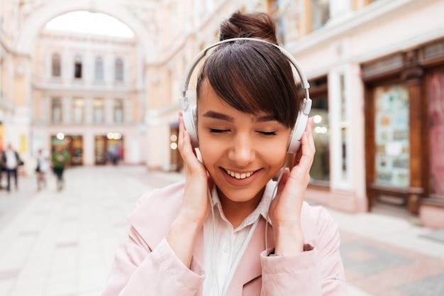 Portret van een glimlachende leuke jonge vrouw het luisteren muziek met oortelefoons