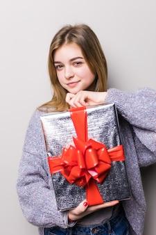Portret van een glimlachende leuke vrouw die giftdoos opent