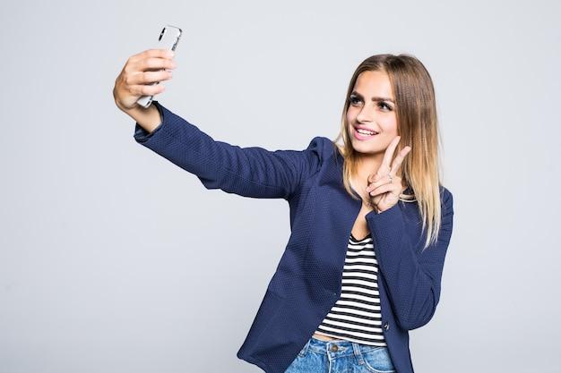 Portret van een glimlachende leuke vrouw die selfiefoto op geïsoleerde smartphone maakt