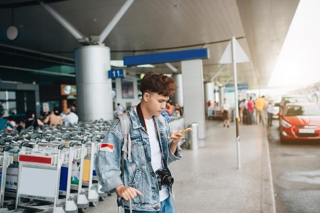 Portret van een glimlachende man die sms't tijdens het wachten op een taxi op de luchthaven