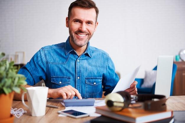 Portret van een glimlachende man die zijn maandelijkse uitgaven berekent