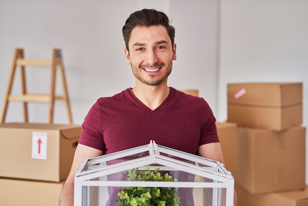 Portret van een glimlachende man die zijn nieuwe flat intrekt