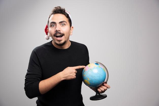 Portret van een glimlachende man in de hoed van de kerstman wijzend op een wereldbol.