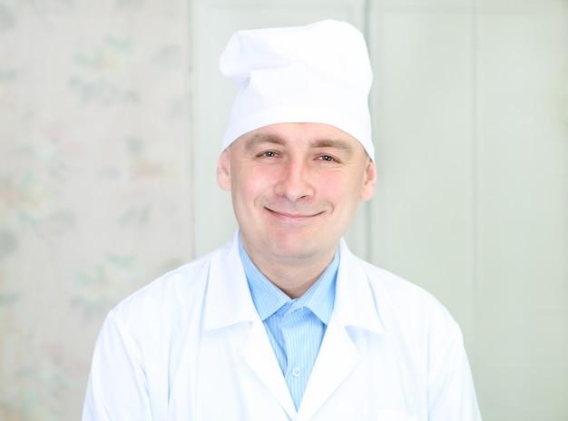 Portret van een glimlachende man in kleding van medisch werker in het interieur
