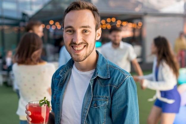 Portret van een glimlachende man op een feestje