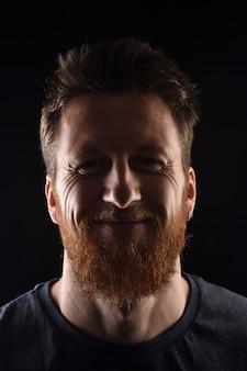 Portret van een glimlachende man op zwart