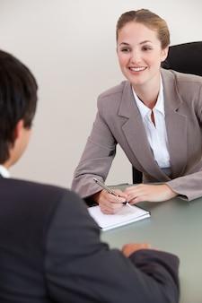 Portret van een glimlachende manager die een mannelijke kandidaat interviewt