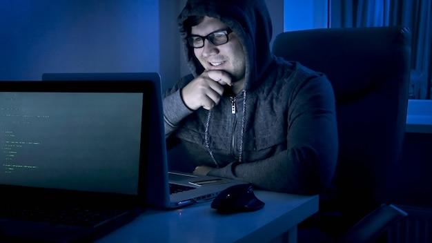 Portret van een glimlachende mannelijke hacker die op laptop kijkt na het stelen van geld en het plegen van cybercriminaliteit.