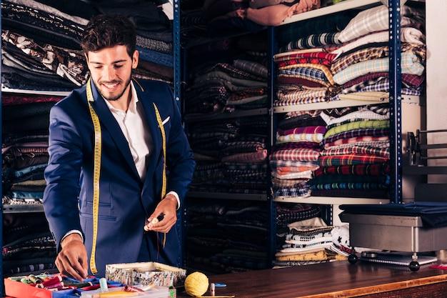 Portret van een glimlachende mannelijke kleermaker die in zijn workshop werkt
