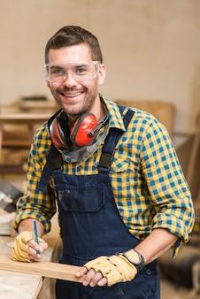 Portret van een glimlachende mannelijke timmerman die houten plank en potlood houdt