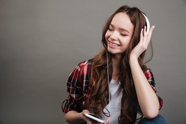 Portret van een glimlachende meisjestiener die van muziek met hoofdtelefoons genieten