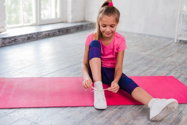 Portret van een glimlachende meisjeszitting op oefeningsmat die haar schoenveter binden