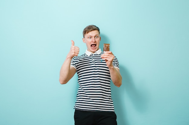 Portret van een glimlachende mens die creditcard toont die over blauwe achtergrond wordt geïsoleerd