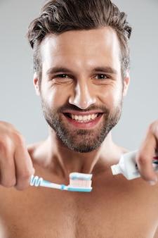 Portret van een glimlachende mens die tandpasta op een tandenborstel zet