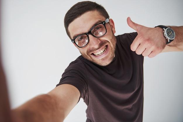 Portret van een glimlachende mens in glazen die duim over wit tonen