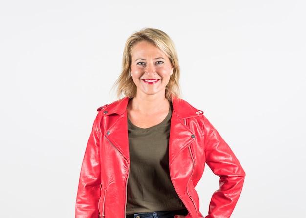 Portret van een glimlachende modieuze blonde rijpe vrouw in rood die jasje op witte achtergrond wordt geïsoleerd