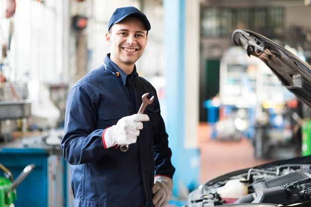 Portret van een glimlachende monteur die een moersleutel in zijn garage houdt