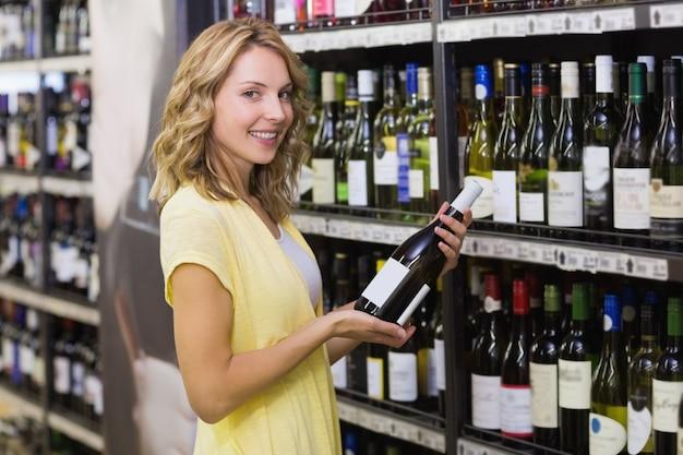 Portret van een glimlachende mooie blondevrouw die een wijnfles in haar handen hebben