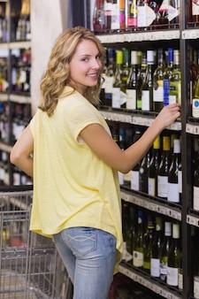 Portret van een glimlachende mooie blondevrouw in de doorgang van de wijnfles