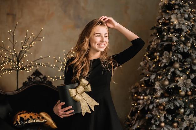 Portret van een glimlachende mooie de giftdoos van de meisjesholding