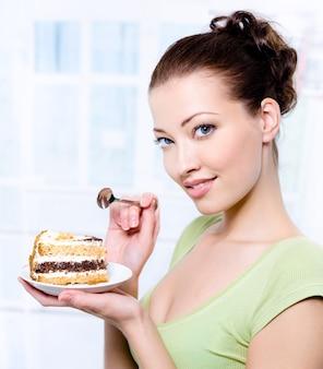 Portret van een glimlachende mooie jonge vrouw met een zoete koek