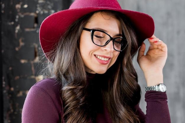 Portret van een glimlachende mooie jonge vrouw met roze hoed en zwarte bril